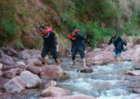 2003-2016年,13年的时间里每次遇到涨水冲毁公路,罗校长和其他老师都要背孩子过河